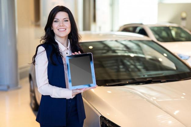 Stijlvolle verzekeringsagent die zich dichtbij de auto bevindt en een tablet houdt Premium Foto