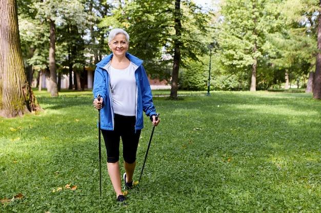 Stijlvolle vrolijke senior oudere vrouw gekleed in sportkleding bewonderen van de prachtige wilde natuur op rustige zomerochtend, wandelen met behulp van speciale stokken, met vrolijke brede glimlach Gratis Foto