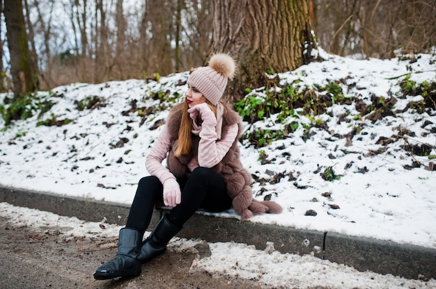 Stijlvolle vrouw in bontjas en hoofddeksels op winterdag op vergadering grens ofroad. Premium Foto