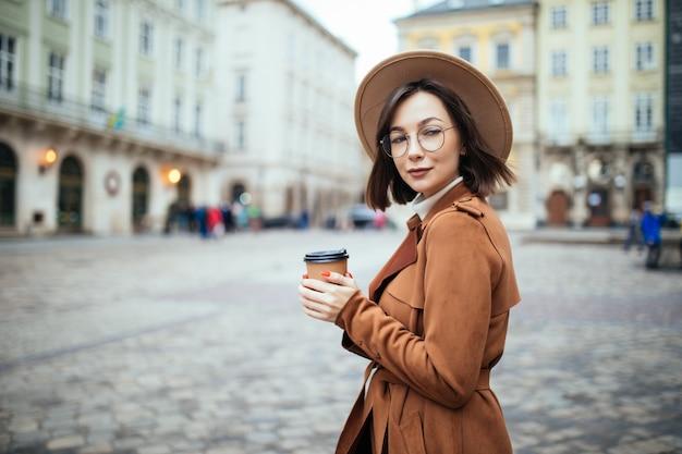 Stijlvolle vrouw in brede hoed koffie drinken op herfst stad Gratis Foto