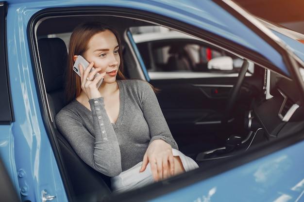 Stijlvolle vrouw in een autosalon Gratis Foto