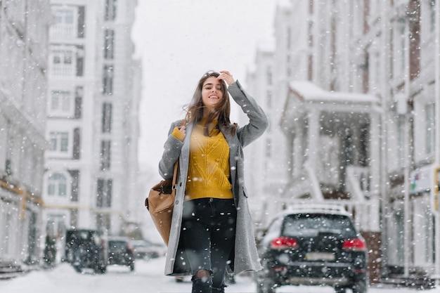 Stijlvolle vrouw in gebreide gele trui poseren onder sneeuwval op straat. outdoor portret van schattige dame in grijze jas genieten van sneeuw Gratis Foto