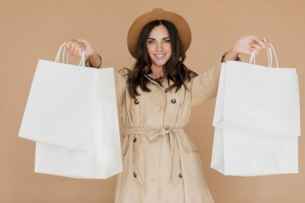 Stijlvolle vrouw in jas met winkelnetten in beide handen Gratis Foto