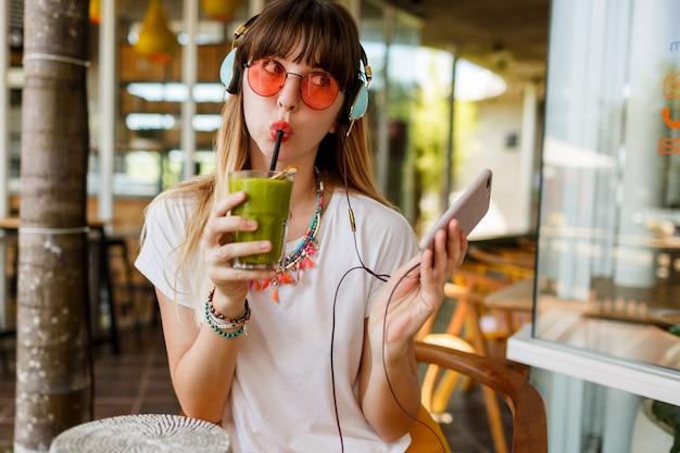 Stijlvolle vrouw in roze bril genieten van groene gezonde smoothie, muziek luisteren door oortelefoons, met mobiele telefoon. Gratis Foto