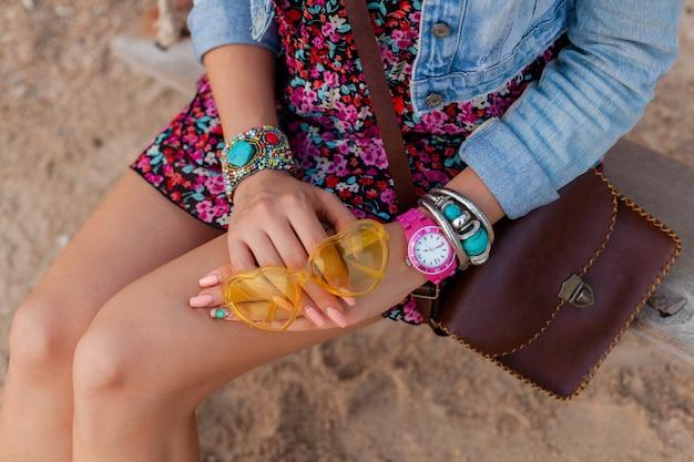 Stijlvolle vrouw in vakantie op beachhands met kleurrijke gele sunglasess accessoires sieraden en tas Gratis Foto