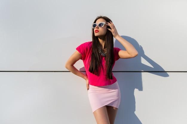 Stijlvolle vrouw in zomerkleding en zonnebril poseren over witte stedelijke muur. Gratis Foto