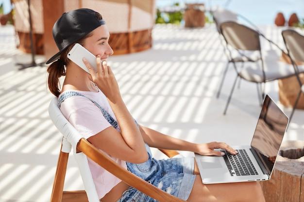 Stijlvolle vrouw in zwarte pet, casual wit t-shirt, berichten in online chat op laptopcomputer, praat met beste vriend op slimme telefoon Gratis Foto