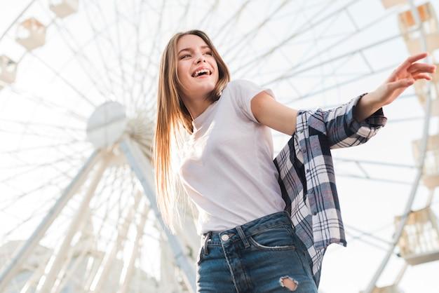 Stijlvolle vrouw poseren in de buurt van reuzenrad Gratis Foto