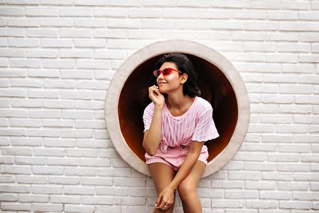 Stijlvolle vrouw poseren op dichtgemetseld muur. buiten schot van vrolijke vrouw in roze zonnebril. Gratis Foto