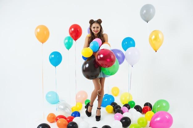 Stijlvolle vrouwelijke hipster poseren met grote ballonnen op wit Gratis Foto