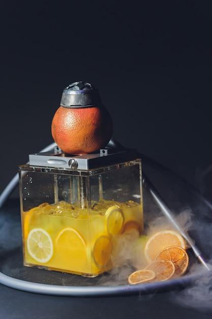 Stijlvolle waterpijp met de aroma-grapefruit voor ontspanning. grapefruit shisha. waterpijp lounge. Premium Foto