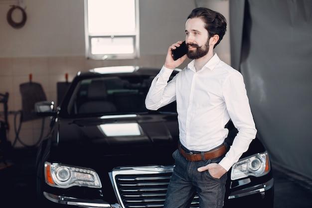 Stijlvolle zakenman die in de buurt van de auto werkt Gratis Foto