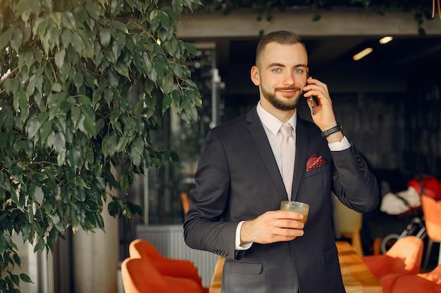 Stijlvolle zakenman in een zwart pak werken in een café Gratis Foto