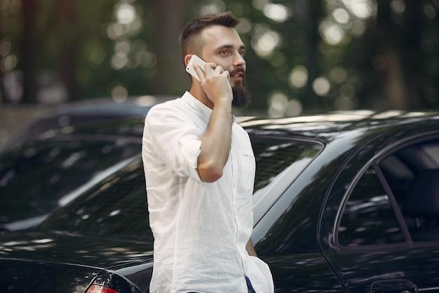 Stijlvolle zakenman permanent in de buurt van de auto en gebruik mobiele telefoon Gratis Foto