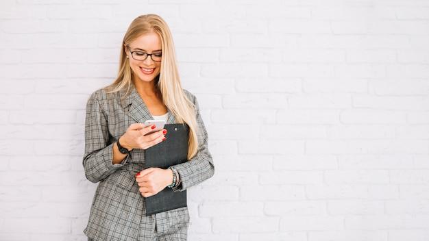 Stijlvolle zakenvrouw met behulp van smartphone Gratis Foto