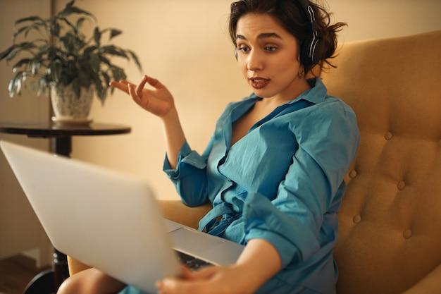 Stijlvolle zelfverzekerde jonge vrouw koptelefoon zittend op de bank met laptop die deelnemen aan zakelijke online groepsbijeenkomst met behulp van webcam conferentie chat, emotioneel gebaren, brainstormen met collega's Gratis Foto