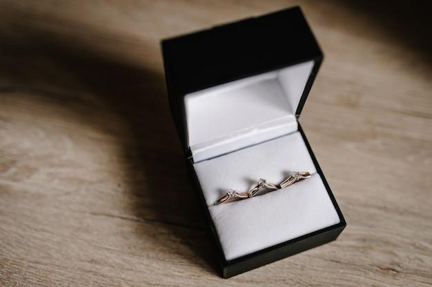 Stijlvolle zilveren oorbellen, gouden ring met diamanten in een geschenkverpakking Premium Foto