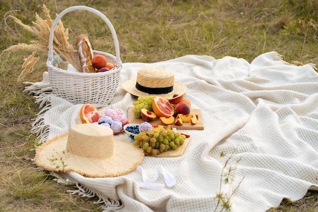 Stijlvolle zomerpicknick op een witte deken. Premium Foto