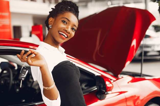Stijlvolle zwarte vrouw in een autosalon Gratis Foto