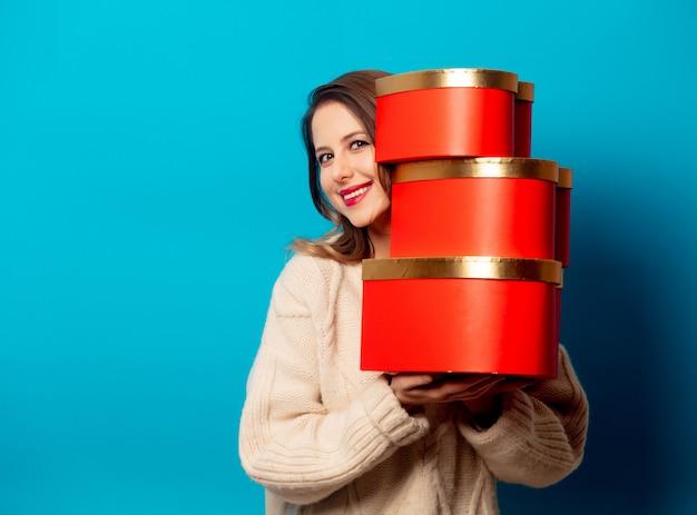 Stijlvrouw in sweater met giftdozen op blauwe muur Premium Foto
