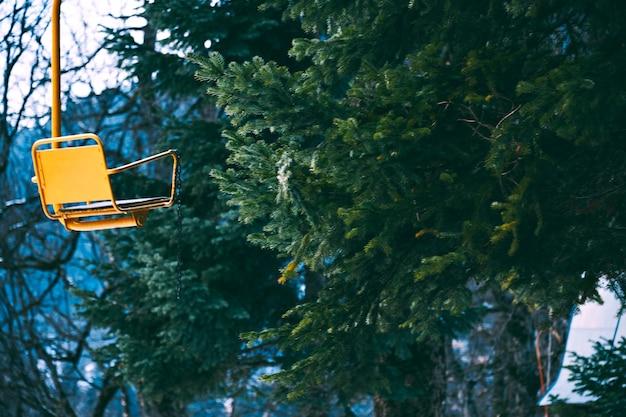 Stilistische foto van oude vintage grunged gele lege skiliftstoel geïsoleerd aan de linkerkant, bahinf pijnboomtakken in winter woud, focus op stoel Gratis Foto