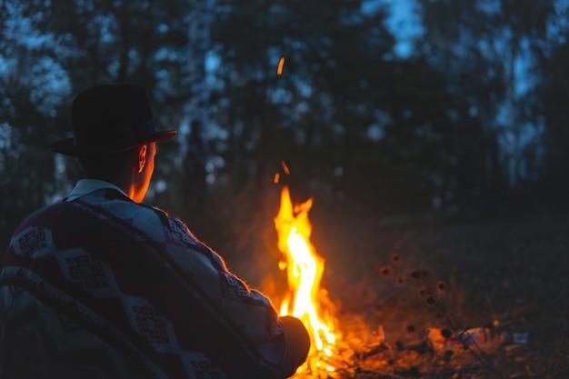 Stille tijd in de nacht bij het kampvuur. man in poncho en hoed zit bij het vuur in het bos Premium Foto