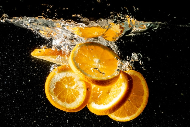 Stilleven dat van stukjes sinaasappel is ontsproten die onder het water vallen en een grote plons maken Gratis Foto