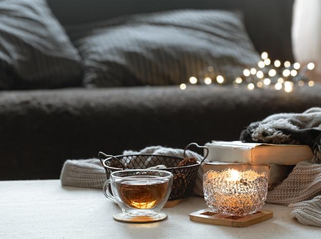 Stilleven met een kopje thee, een theepot, boeken en een brandende kaars in een kandelaar met bokeh. Gratis Foto