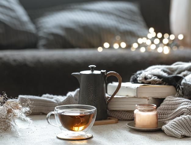 Stilleven met een kopje thee, een theepot, boeken en een kaars in een kandelaar met bokeh. Gratis Foto