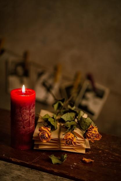 Stilleven met gedroogde rozen kaars en bos van oude brieven Premium Foto