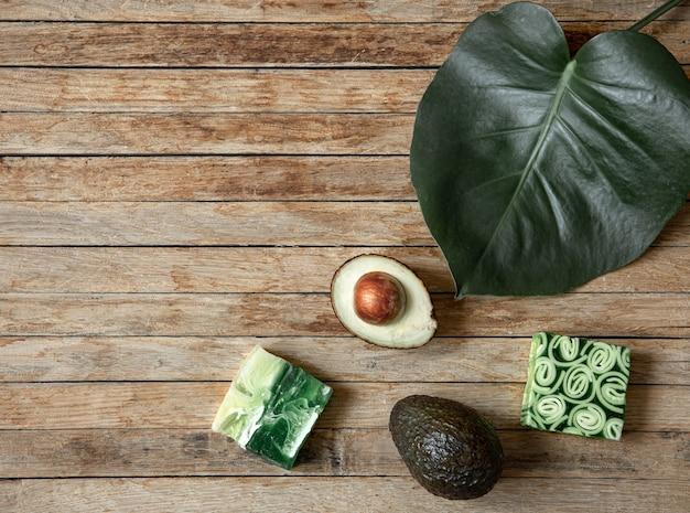 Stilleven met handgemaakte zeep, natuurlijk blad en avocado bovenaanzicht. biologische cosmetica en schoonheidsconcept. Gratis Foto