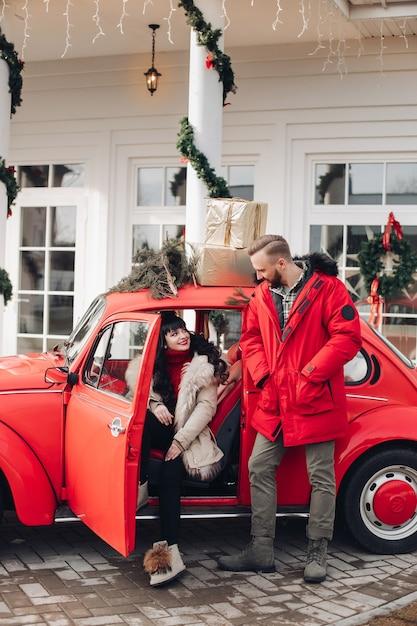 Stock foto van een mooie vrouw en knappe man in vintage rode auto met geschenken bovenop. Gratis Foto