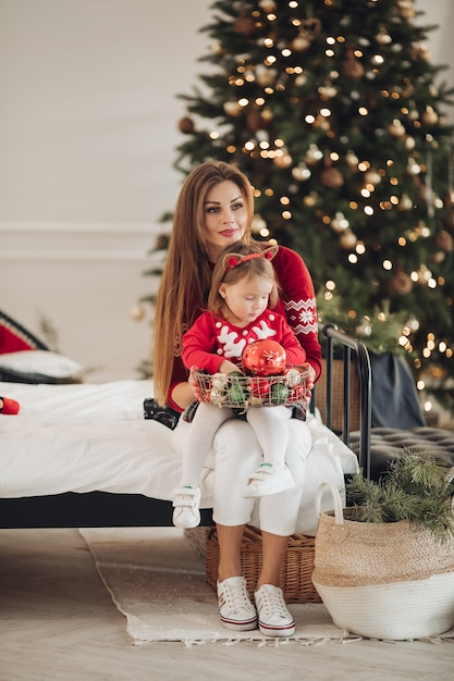 Stock foto van liefdevolle moeder in groene jurk geven haar dochtertje in pyjama jurk een kerstcadeau. ze staan naast een prachtig versierde kerstboom onder sneeuwval. Gratis Foto