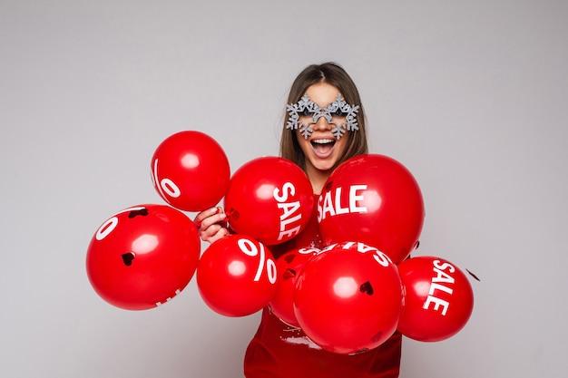 Stock foto van vrij brunette vrouw in mooie glazen met sneeuwvlokken houden lucht ballonnen Premium Foto