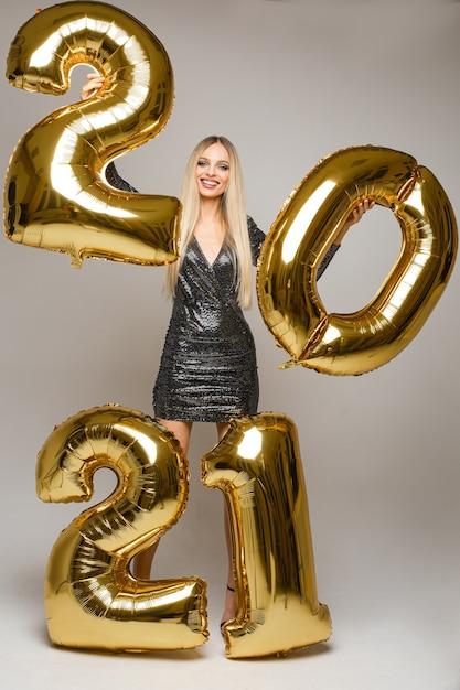 Stock foto - vrolijk meisje met lang blond haar in feestelijke cocktailjurk met gouden opgeblazen ballonnen Premium Foto
