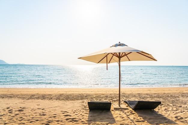 Stoelparaplu en zitkamer op de mooie strand overzeese oceaan op hemel Gratis Foto
