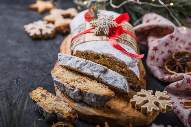 Stollen. gesneden zelfgemaakte kerstdessert stol met gedroogde bessen en noten op stenen rustieke tafel met kaneel, stukjes sinaasappel, kerstboomtakken, peperkoek, selectieve aandacht Premium Foto