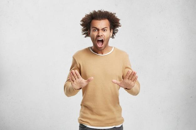 Stop alsjeblieft! geïrriteerde woedende man heeft afro kapsel maakt stop gebaar Gratis Foto