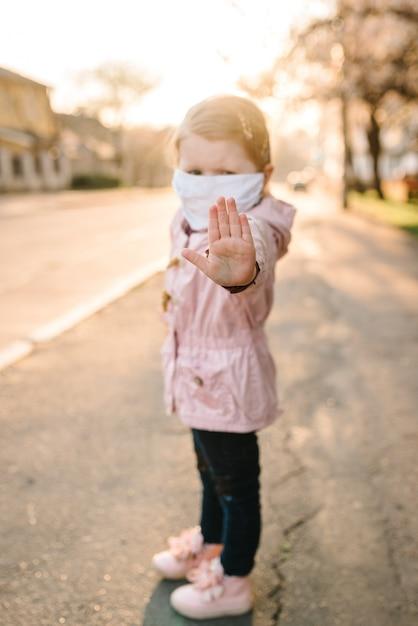 Stop de coronavirus- en virusepidemische ziekten. gezond kind in medisch beschermend masker dat gebaareinde toont. bescherming en preventie van de gezondheid tijdens griep en besmettelijke uitbraak Premium Foto