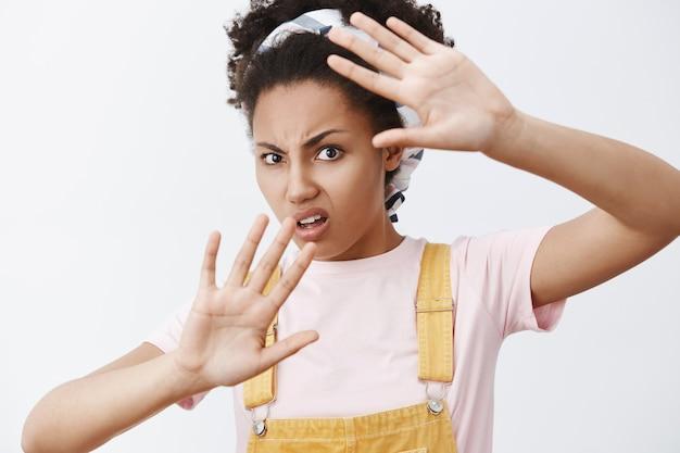 Stop met het rond mijn gezicht te zwaaien. portret van ontevreden en gehinderd geërgerd afro-amerikaanse moderne vrouw in gele overall en hoofdband, bedekt met opgeheven handpalmen, fronsend Gratis Foto
