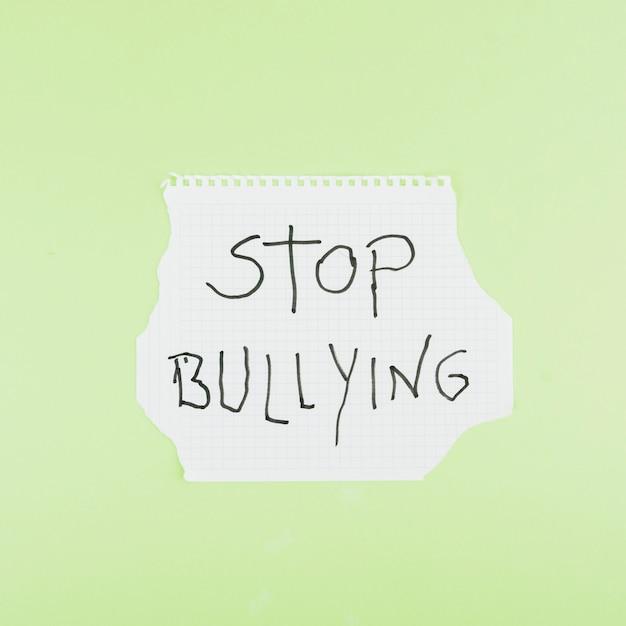 Stop met pesten slogan op gekwadrateerde vel papier Gratis Foto