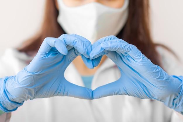 Stop sarscov, mers-cov, chinees virus covid-19. de close-upvrouwen dienen blauwe medische handschoenen in tonen hartteken. concept van bescherming tegen hiv. doctor in de blauwe medische handschoenen en beschermend masker. Premium Foto