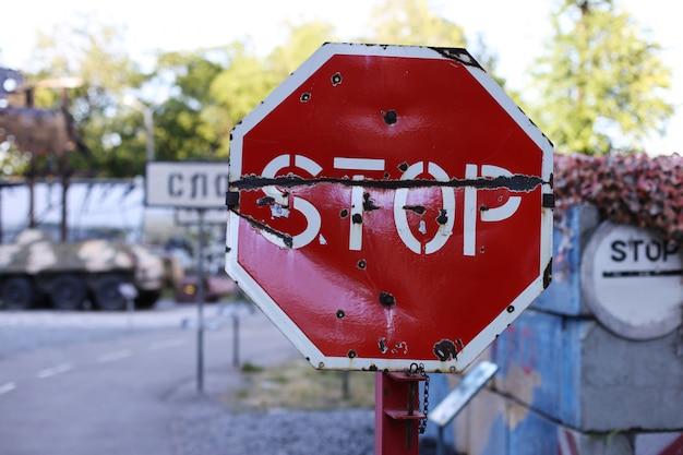 Stop verkeersbord, op het toneel van vijandelijkheden. kogelgaten in metaal. Premium Foto