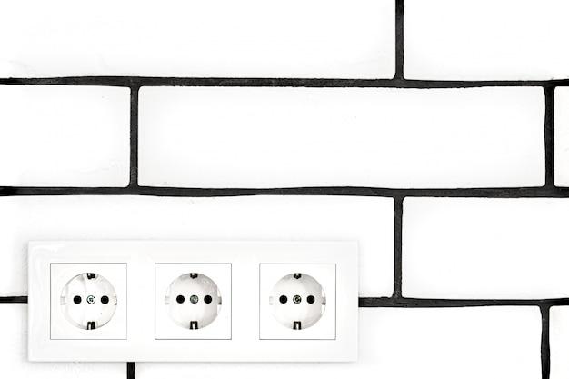 Stopcontacten tegen een witte bakstenen muur. Gratis Foto