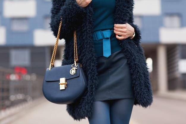 Straat, heldere stijl. een jong meisje in een blauwe bontjas met een handtas in hakken. details. Premium Foto