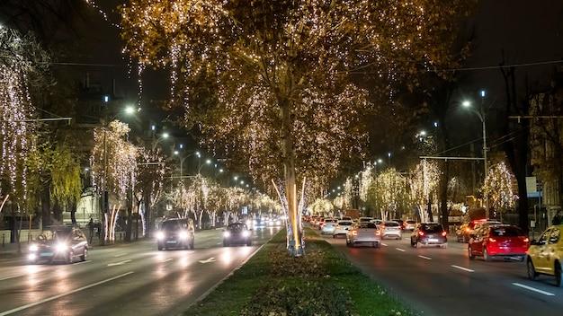 Straatbeeld van de stad 's nachts, auto's die op de weg rijden, veel kerstverlichting in boekarest, roemenië Gratis Foto