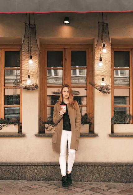 Straatportret van een stijlvol meisje in volle gang, het dragen van lentekleren, permanent met een kopje koffie in haar handen en op zoek naar de camera Premium Foto