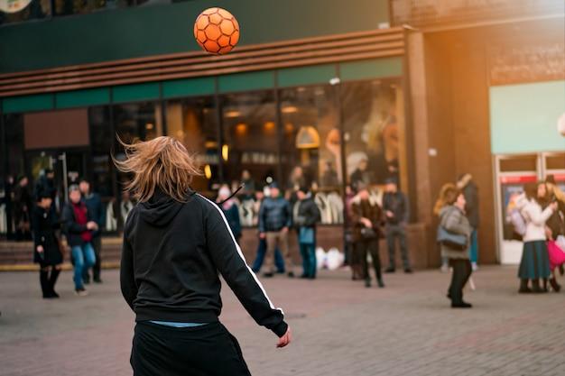 Straatvoetbal freestyle artiest. een jonge man doet voetbaltrucs op straat Premium Foto