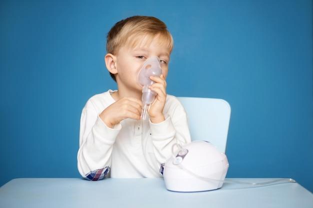 Strabismusjongen die inhalatie met een verstuiver op een blauw doet Premium Foto