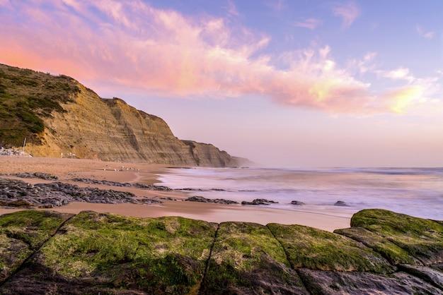 Strand omgeven door de zee en kliffen bedekt met mos onder een bewolkte hemel tijdens de zonsondergang Gratis Foto